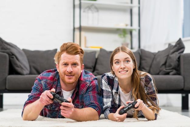 Portrait, sourire, jeune couple, coucher tapis, jouer, jeu vidéo
