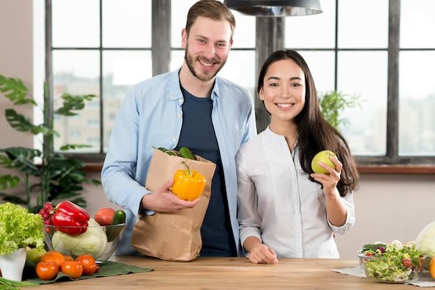 Portrait, de, sourire, jeune couple, debout, derrière, comptoir cuisine, bois, tenue, poivron jaune, et, pomme verte
