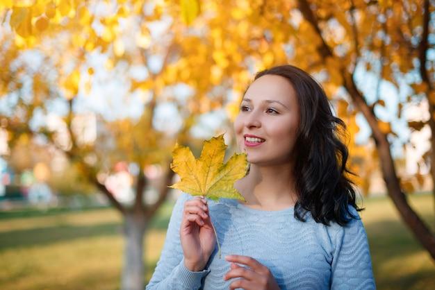 Portrait, de, sourire, jeune femme, à, automne, feuilles, devant, feuillage