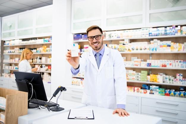 Portrait de sourire pharmacien caucasien tenant des vitamines en pharmacie.