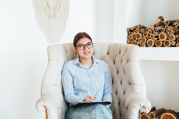 Portrait de sourire psychologue femme caucasienne assis dans un fauteuil sur le lieu de travail, tenant un dossier avec des papiers pour les notes.
