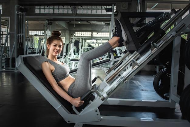 Portrait sport fille faisant la jambe appuie dans la salle de gym avec souriant concept de visage, de remise en forme et d'exercice.