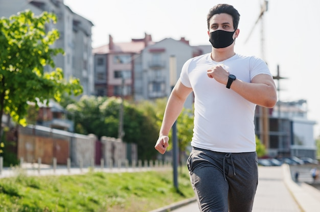 Portrait sport homme arabe en masque facial médical noir exécuté en plein air pendant la quarantaine des coronavirus.
