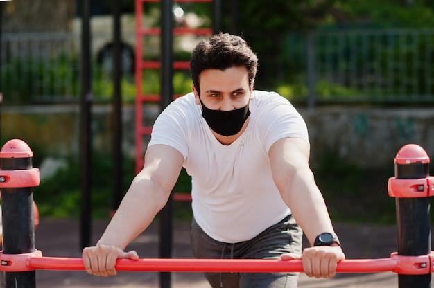 Portrait sport homme arabe en masque facial médical noir faisant des exercices d'entraînement dans un gymnase en plein air pendant la quarantaine des coronavirus.