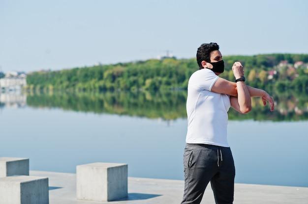 Portrait sport homme arabe en masque facial médical noir faisant des exercices d'entraînement du matin contre le lac pendant la quarantaine des coronavirus.