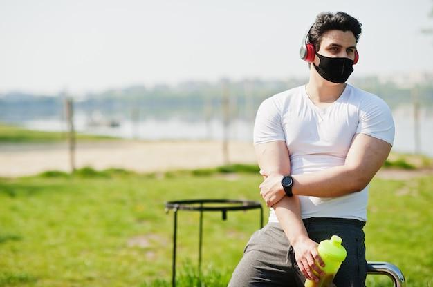 Portrait sport homme arabe en masque facial médical noir posé en plein air avec des écouteurs pendant la quarantaine des coronavirus.