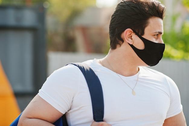 Portrait sport homme arabe en masque facial médical noir avec sac à dos posé contre triangle jaune pendant la quarantaine des coronavirus.
