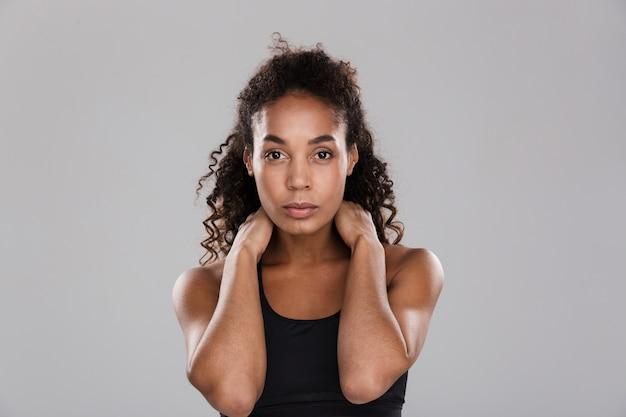 Portrait d'une sportive afro-américaine confiante isolée sur mur gris, debout