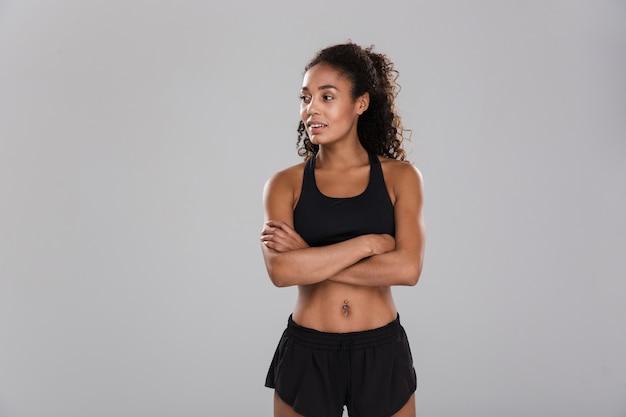 Portrait d'une sportive afro-américaine souriante isolée sur mur gris, debout, à l'écart