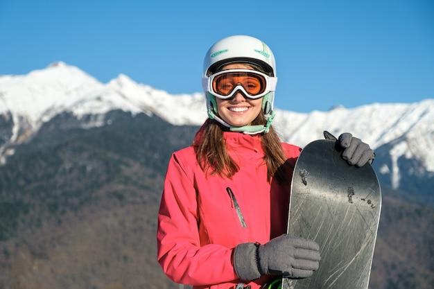 Portrait d'une sportive portant un casque et un masque avec snowboard à la main en regardant la caméra
