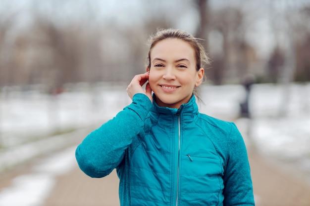 Portrait de sportive en tenue chaude debout dans un parc public par temps de neige et mettant des écouteurs. sports d'hiver, musique, loisirs, technologie