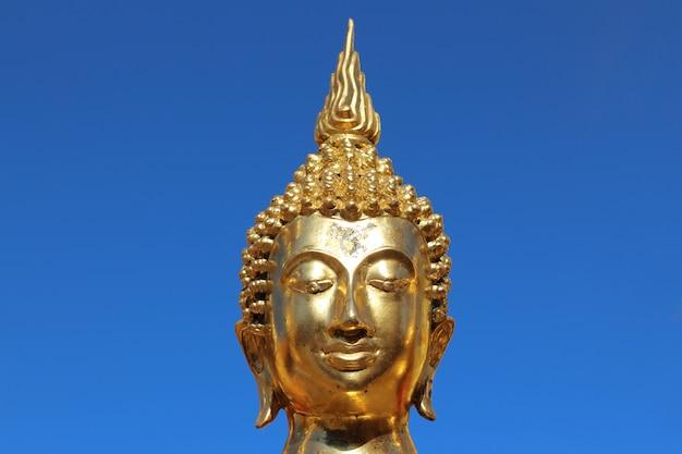 Portrait une statue de bouddha en or sur fond de ciel bleu