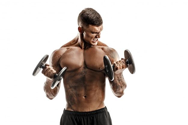 Portrait en studio de beau bodybuilder topless, faire des exercices sur les biceps contre une scène blanche