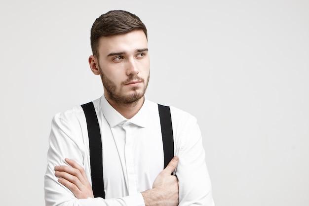 Portrait en studio de beau jeune homme d'affaires mal rasé en tenue de soirée en gardant les bras croisés tout en pensant aux concepts, idées, solutions, stratégie et perspectives concernant son nouveau projet d'entreprise