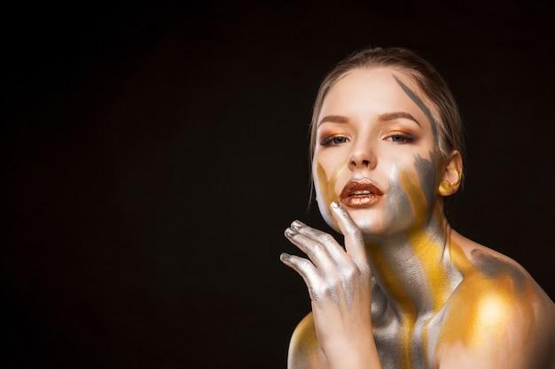 Portrait de studio de beauté d'une femme blonde luxueuse avec de la peinture or et argent sur ses épaules et son visage. espace pour le texte