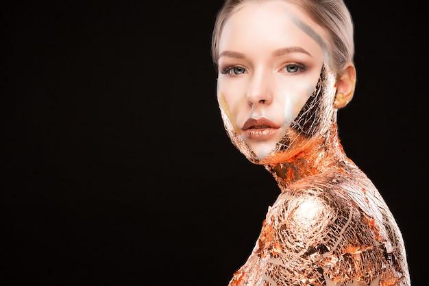 Portrait de studio de beauté d'un modèle blond séduisant avec une feuille d'or sur ses épaules. espace pour le texte