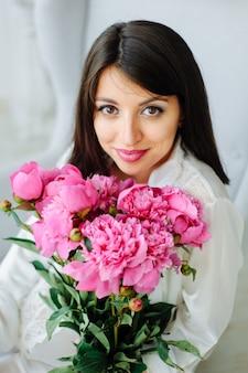 Portrait en studio de beauté. modèle romantique femme avec des fleurs de pivoine. tir de haute couture.
