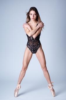 Portrait en studio d'une belle fille avec une silhouette sportive dans un body en dentelle sur pointe