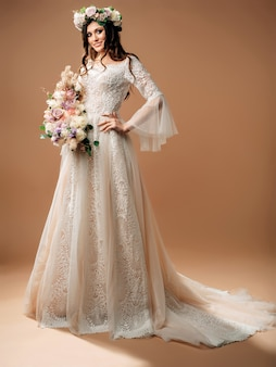 Portrait en studio de la belle mariée en robe de mariée magnifique avec grand bouquet.