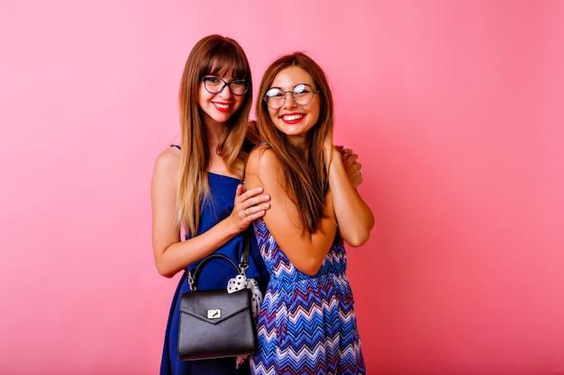Portrait en studio de deux amis heureux femmes élégantes sortis