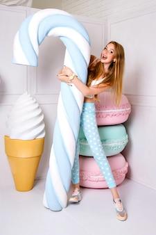 Portrait en studio drôle de femme assez gaie tenant une énorme canne à sucre, de faux gros macarons et de la crème glacée sur fond, des couleurs pastel.