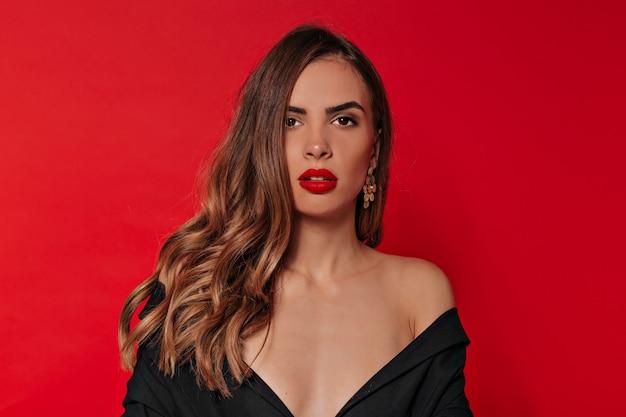 Portrait en studio d'élégante dame élégante avec maquillage de soirée en robe noire aux épaules nues