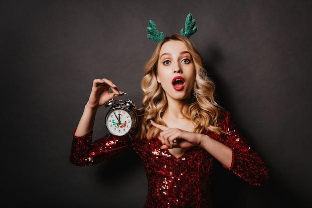 Portrait en studio d'une femme adolescente surprise avec horloge