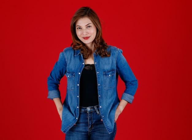 Portrait en studio d'une femme asiatique de 45 ans portant des vêtements en jean et posant devant la caméra avec un visage souriant et une confiance en soi sur fond rouge.