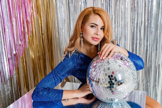 Portrait en studio d'une femme blonde élégante avec un maquillage parfait et une boule disco