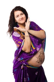 Portrait en studio d'une femme enceinte heureuse en sari indien, un ventre de femme enceinte peint au henné