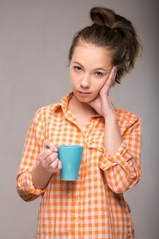 Portrait en studio d'une femme endormie dans une chemise orange avec une tasse de café à la main