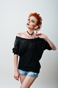 Portrait en studio de la fille aux cheveux rouge sur une blouse noire et un short en jean avec un maquillage foncé et brillant