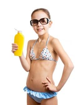 Portrait en studio d'une fille souriante heureuse posant avec une lotion solaire
