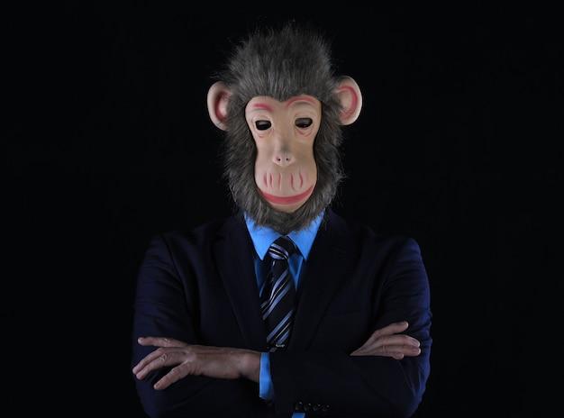 Portrait en studio d'un homme d'affaires portant un masque de singe