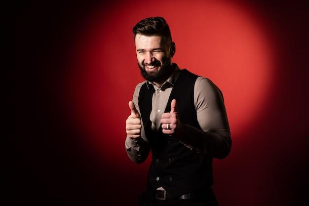 Portrait en studio d'un homme barbu dans un gilet sur fond rouge. la main de l'homme montre un geste de classe