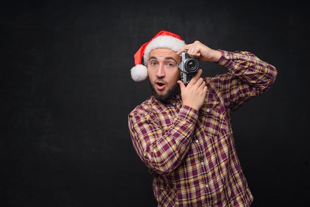 Portrait en studio d'homme barbu drôle et surpris portant bonnet de noel tenant un appareil photo rétro, faisant une photo. espace pour le texte. noir