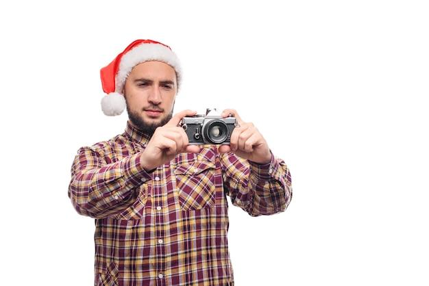Portrait en studio d'homme barbu portant bonnet de noel tenant un appareil photo rétro, faisant une photo. fond blanc isolé
