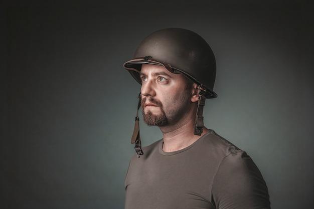 Portrait en studio de l'homme avec un casque militaire à la recherche de suite.