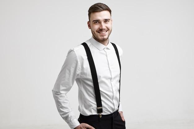 Portrait en studio isolé de succès beau jeune homme d'affaires caucasien avec barbe taillée souriant joyeusement à la caméra après avoir signé un bon contrat. concept d'entreprise, de succès, de style et de mode