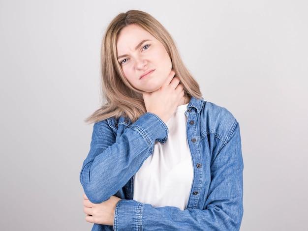 Portrait en studio de jeune femme blonde toux malsaine en t-shirt blanc et chemise en jean souffrant de rhume et de grippe