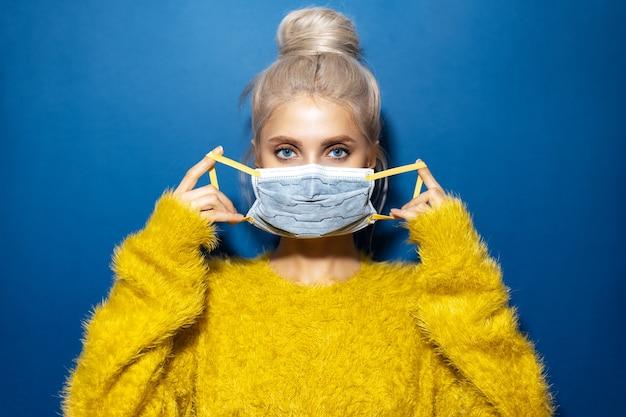 Portrait en studio de jeune fille aux cheveux blonds, portant un masque médical contre le coronavirus et un pull jaune, sur fond texturé de couleur bleu fantôme.