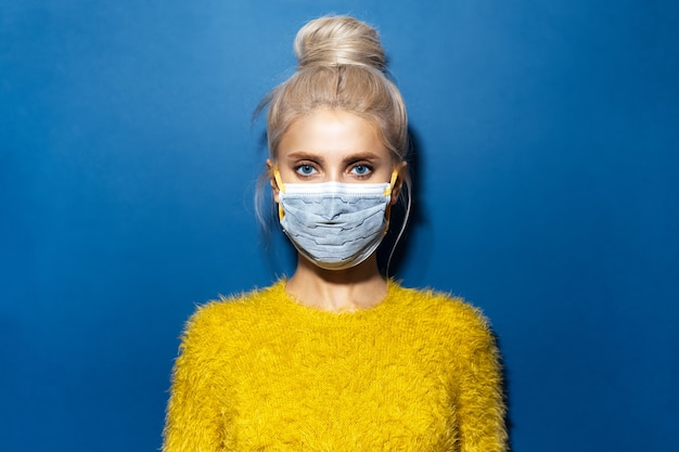 Portrait en studio de jeune fille aux cheveux blonds, portant un masque médical contre le coronavirus et un pull jaune, sur fond texturé de couleur bleue.