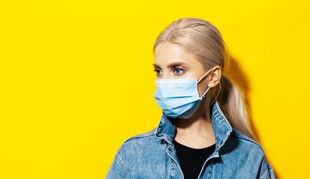 Portrait en studio de jeune fille blonde aux yeux bleus en veste en jean portant un masque médical contre le coronavirus sur fond jaune.