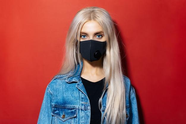 Portrait en studio de jeune fille blonde aux yeux bleus en veste en jean portant un masque médical noir contre le coronavirus sur fond rouge.
