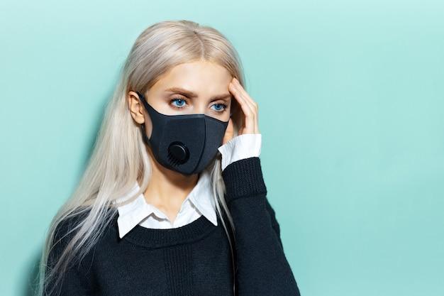 Portrait en studio de jeune fille blonde, ayant mal à la tête, portant un masque respiratoire de couleur noire, contre le virus. fond de couleur cyan, aqua menthe.