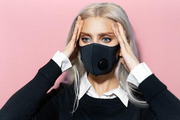 Portrait en studio d'une jeune fille blonde tenant les mains sur la tête à cause de douleurs, portant un masque respiratoire contre le coronavirus sur fond de couleur rose pastel.