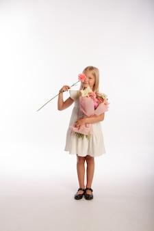 Portrait en studio de jolie fille blonde en robe blanche avec beau bouquet cadeau, fond blanc, mise au point sélective
