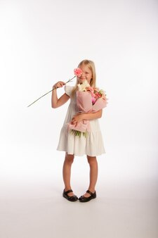Portrait en studio de jolie fille blonde en robe blanche avec beau bouquet cadeau