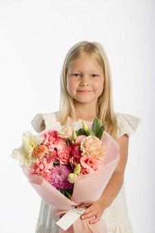 Portrait en studio de jolie fille blonde en robe blanche avec panier en bois de fleurs, mur blanc, mise au point sélective
