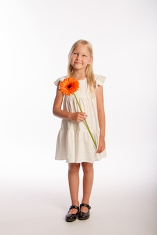 Portrait en studio de jolie fille blonde en robe blanche avec une seule fleur de gerbera, fond blanc, mise au point sélective
